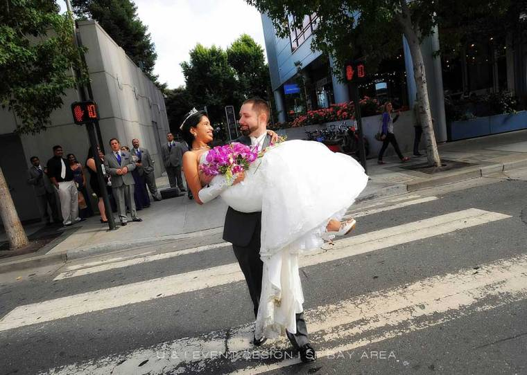groom carrying bride while posing for photos on the streets of san francisco at event by bay area wedding planner
